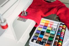 Macchina per cucire, panno rosso ed accessori di cucito Immagine Stock