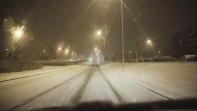 In macchina su una strada nevosa in una città di inverno stock footage