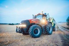 Macchinario agricolo e trattore su un campo raccolto immagini stock