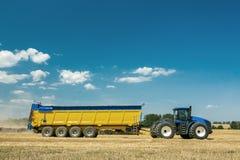 Macchinario agricolo nella priorità alta, realizzante lavoro sulla terra Fotografia Stock