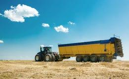 Macchinario agricolo nella priorità alta, realizzante lavoro sulla terra Immagine Stock