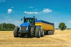 Macchinario agricolo nella priorità alta, realizzante lavoro sulla terra Fotografia Stock Libera da Diritti