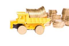 Macchinario di costruzione sopra molte monete dorate Immagine Stock