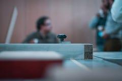 Macchinario di legno di taglio di CNC, operatore con funzionamento blu della camicia immagine stock libera da diritti