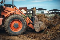 Macchinario industriale al cantiere di lavoro Chiuda su del caricatore dell'escavatore a cucchiaia rovescia che lavora con l'inge immagini stock libere da diritti