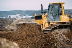 macchinario resistente, dettagli dell'escavatore che spingono terra e che costruiscono strada principale Mattoni che si situano a Immagini Stock Libere da Diritti
