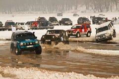 Macchine da corsa fuori strada nel fiume sulla corsa di strada Immagini Stock