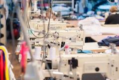 Macchine da cucire industriali in un'officina dell'indumento fotografia stock