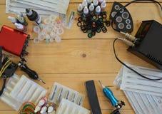 Macchine ed attrezzature del tatuaggio su fondo di legno Fotografie Stock