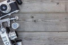 Macchine fotografiche tranquille d'annata sulla tavola di legno di lerciume Fotografia Stock