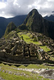 Macchu Picchu. Portrait shot of the ancient Inca city of Macchu Picchu, Peru, close up of ruins with winha Picchu in background and clouds in sky Stock Photo