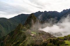 Macchu Picchu för soluppgång som täckas i stigande moln arkivfoto