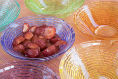 Macedoine strawberries in colored bowls Stock Photos