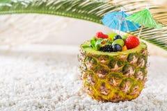 Macedonia di frutta dolce in ananas sulla spiaggia sabbiosa Immagine Stock
