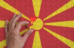 Macedonia flag is depicted on a puzzle, which the man`s hand completes to fold.  stock illustration