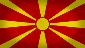 Macedonia flag. Growing sun in the center of macedonia flag with eight rays from the center to the outside, red and yellow fabric texture flag, texture Stock Photos