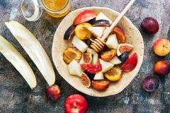 Macedonia fresca del melone, dei fichi, delle mele, delle prugne e del miele su un fondo rustico scuro, vista superiore Il concet immagini stock libere da diritti