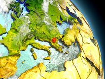 Macedonia from space. Macedonia in red on model of planet Earth with embossed countries and visible country borders. 3D illustration with clouds and reflective Stock Photos