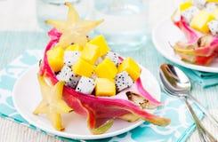 Macedonia tropicale in pitahaya, mango, ciotole di frutta del drago con un vetro di succo Immagine Stock