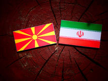 Macedonian flag with Iranian flag on a tree stump isolated. Macedonian flag with Iranian flag on a tree stump Stock Images