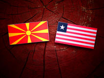 Macedonian flag with Liberian flag on a tree stump isolated. Macedonian flag with Liberian flag on a tree stump Royalty Free Stock Photography