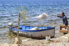 Macedonian workers loading garbage into a boat Royalty Free Stock Images