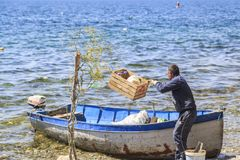 Macedonian workers loading garbage into a boat Royalty Free Stock Photo