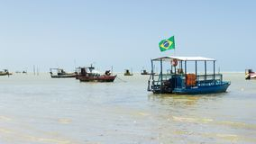 Maceio, Brazil - September, 05 2017. Brazilian coast with severa. L boats moored on the coast. The flag of Brazil is in one of them Royalty Free Stock Images
