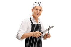 Macellaio che affila il suo coltello fotografie stock