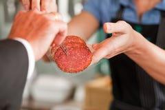 Macellaio che mostra le bistecche della carne fresca al cliente Fotografia Stock Libera da Diritti