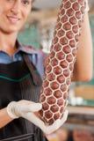 Macellaio femminile che mostra salsiccia fresca Immagini Stock