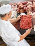 Macellaio Holding Minced Meat all'armadietto di esposizione fotografia stock
