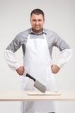 Macellaio professionista che sorride dietro la tavola. immagini stock libere da diritti