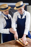 Macellaio Teaching Apprentice How per preparare bistecca di controfiletto Fotografia Stock