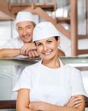 Macelleria femminile felice di With Colleague At del macellaio Fotografie Stock