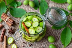 A glass jar filled with unripe walnuts, lemon and spices royalty free stock images