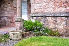 Macetas, flores y helechos viejos por una pared de piedra de una casa Foto de archivo