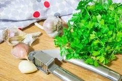 Machacamiento del ajo para añadir al plato Ajo entero y tajado en una tabla de cortar hecha de roble natural Perejil fresco imagen de archivo libre de regalías