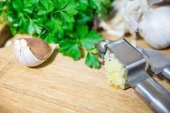 Machacamiento del ajo para añadir al plato Ajo entero y tajado en una tabla de cortar hecha de roble natural Perejil fresco fotos de archivo
