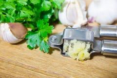 Machacamiento del ajo para añadir al plato Ajo entero y tajado en una tabla de cortar hecha de roble natural Perejil fresco fotografía de archivo libre de regalías