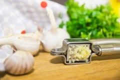 Machacamiento del ajo para añadir al plato Ajo entero y tajado en una tabla de cortar hecha de roble natural Perejil fresco imagenes de archivo