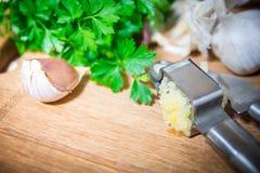 Machacamiento del ajo para añadir al plato Ajo entero y tajado en una tabla de cortar hecha de roble natural Perejil fresco imágenes de archivo libres de regalías