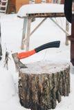 machado com a pilha do punho na madeira desbastada no inverno imagem de stock