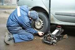 Machanic repairman at tyre fitting with car jack. Mechanic repairman making tyre fitting by using jack for car lifting stock image