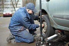 Machanic Schlosser am Reifenbeschlag mit Autosteckfassung Stockfotos