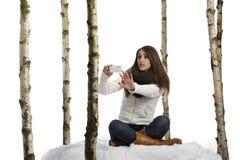 Machen der Fotos im Schnee mit einem Mobiltelefon Stockfoto