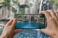 Machen des Fotos Cheonjeyeon-Wasserfalls auf Jeju-Insel, Südkorea mit Handy Aktiver Tourismus in Asien lizenzfreie stockfotos