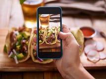 Machen des Fotos der Straßentacos mit Smartphone stockbilder