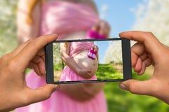 Machen des Fotos des Bauches eines schwangeren Mädchens mit Handy Lizenzfreie Stockfotos