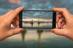 Machen des Fotos des Leuchtturmes im Hafen mit Handy Stockbild